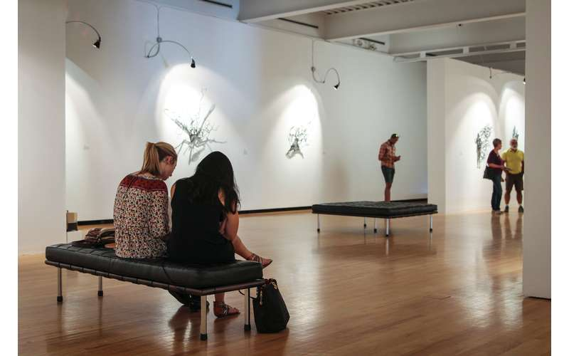 visitors on a bench inside an art gallery space