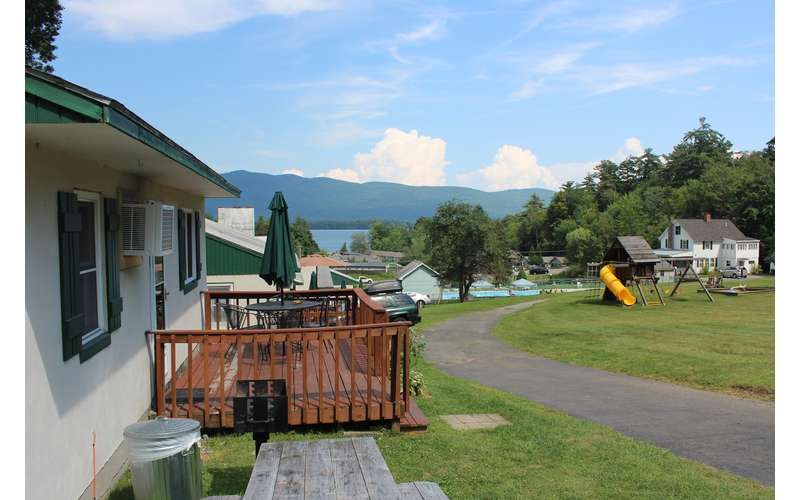 view of cottage with deck from theside with lake, mountains, and a playground in the background