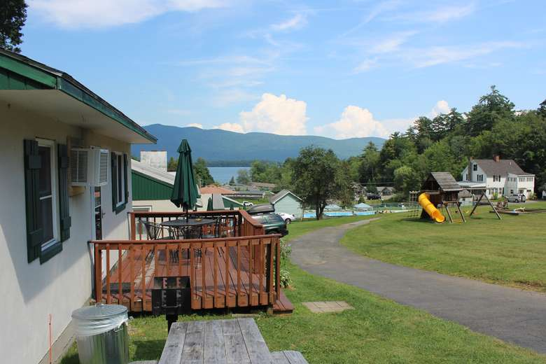 view of cottage with deck from the side with lake, mountains, and a playground in the background