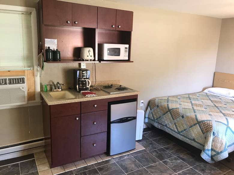 room with bed, mini fridge, microwave, sink