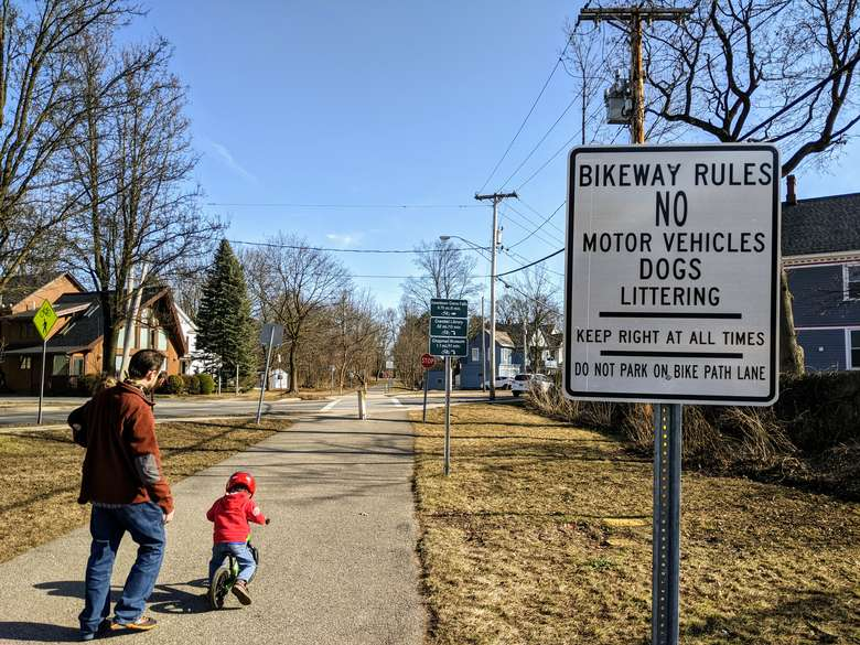 man and child on bike path with no motor vehicles sign