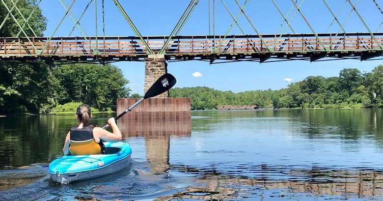 woman kayaking toward a bridge
