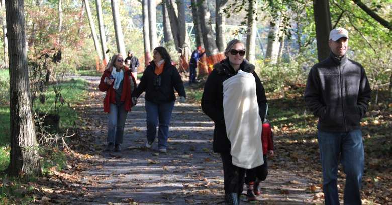 people walking along a paved path in the fall