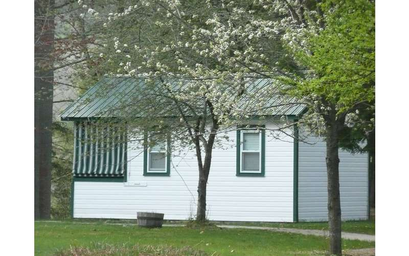 side view of a white cabin near some trees