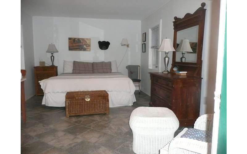 a brown dresser near a queen bed