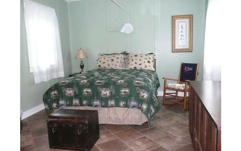 a queen bed with a green blanket and two pillows