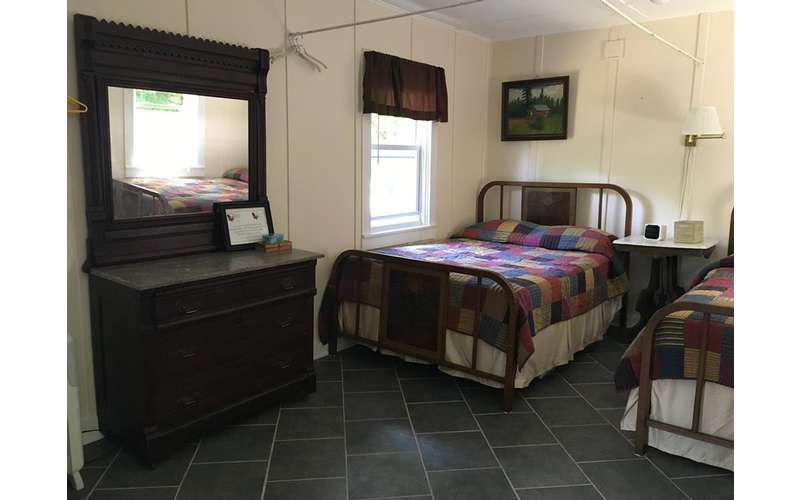 two beds side by side with a dark brown dresser nearby
