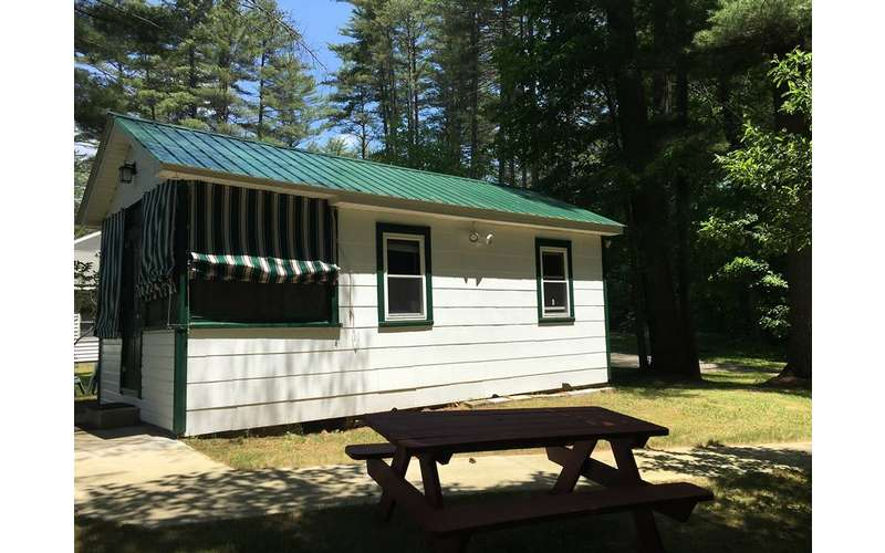 side view of a white cabin near a picnic table