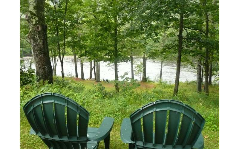 two green chairs facing the river