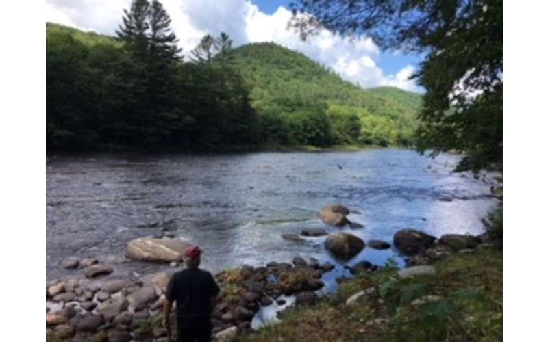 man standing near a river shoreline