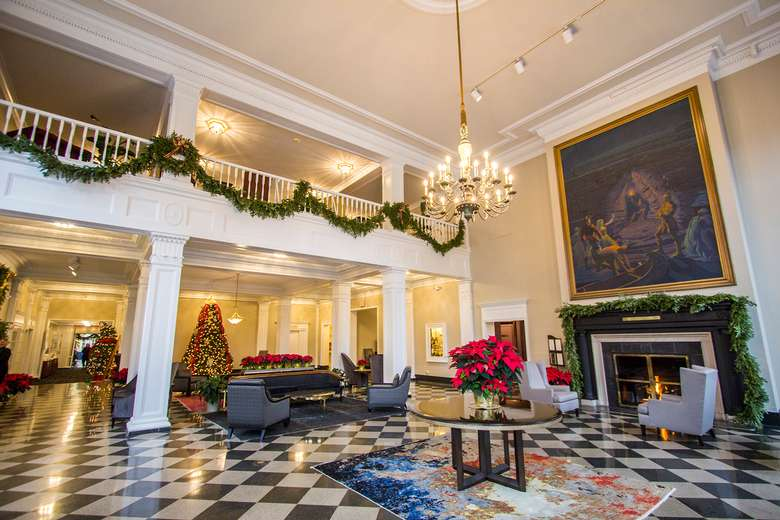 lobby at the queensbury decorated for the holidays with poinsettias and garlands