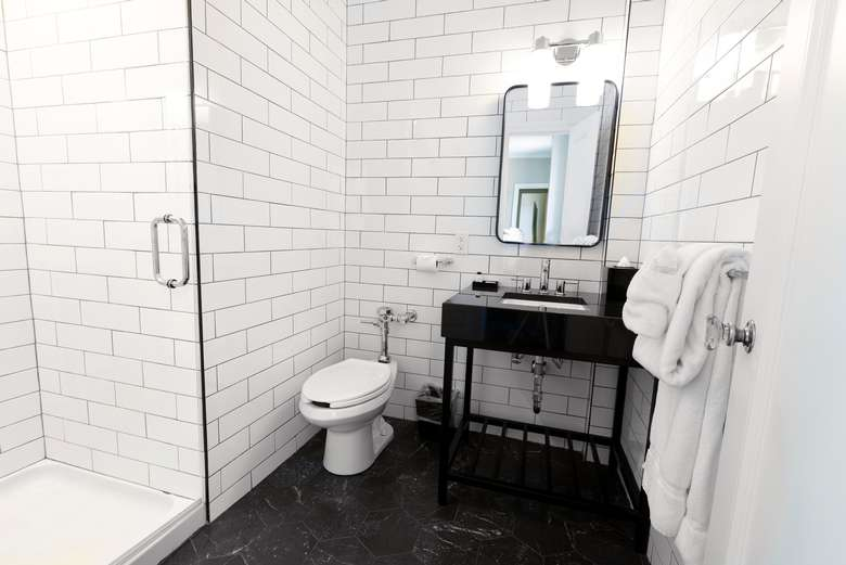queensbury hotel bathroom with white subway tiles and a glass shower door