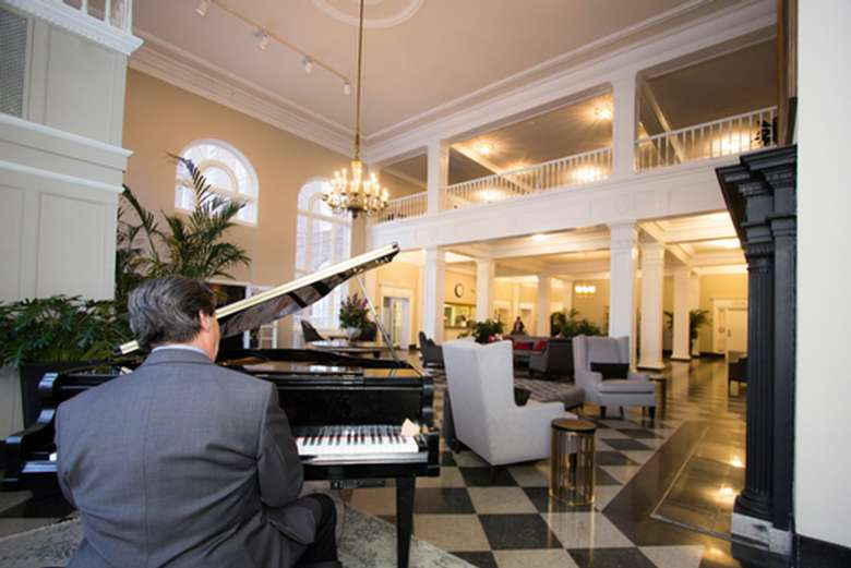 man playing piano in the lobby at the queensbury hotel
