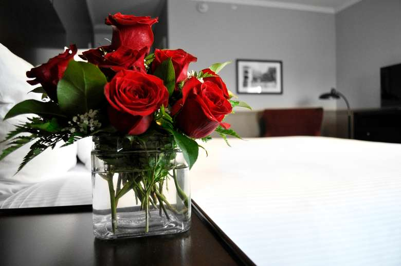 vase of red roses on the nightstand next to a hotel room bed