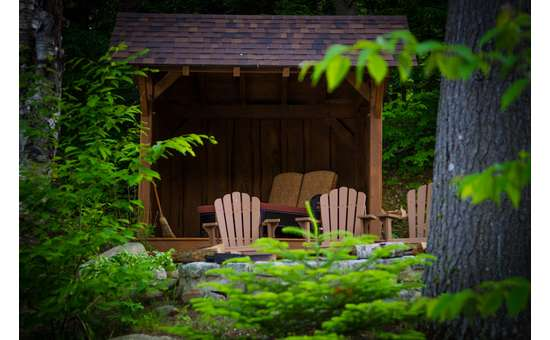 our lean-to;with lounge chairs inside and a fire pit with Adirondack chairs in front