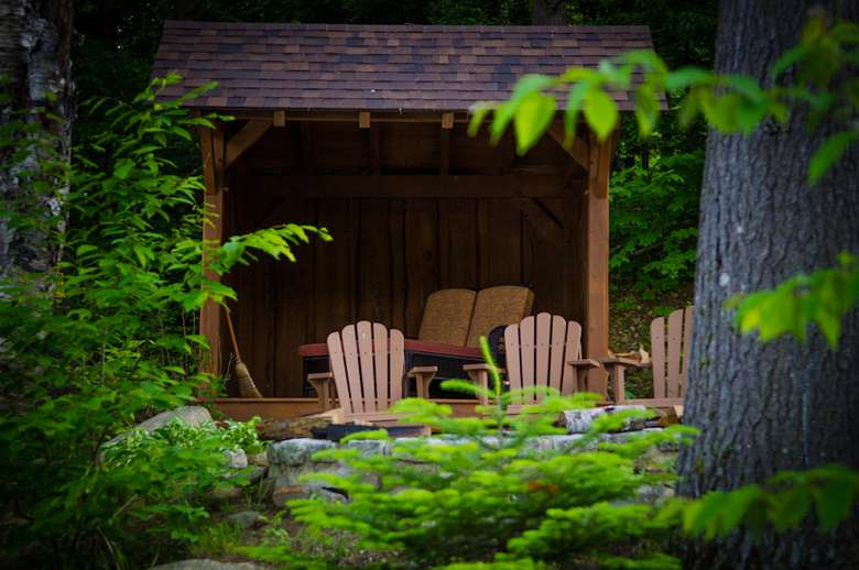 a lean to at the lakes edge with foliage around and Adirondack chairs