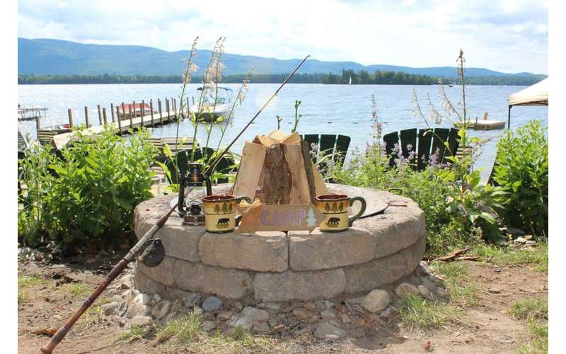 a fire pit with Adirondack-style mugs on it, water in the background
