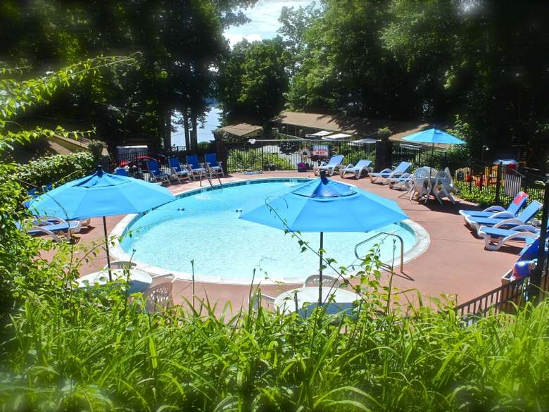 round outdoor pool, fenced in area, pool chairs