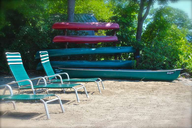 lounge chairs on a beach next to a rack of canoes