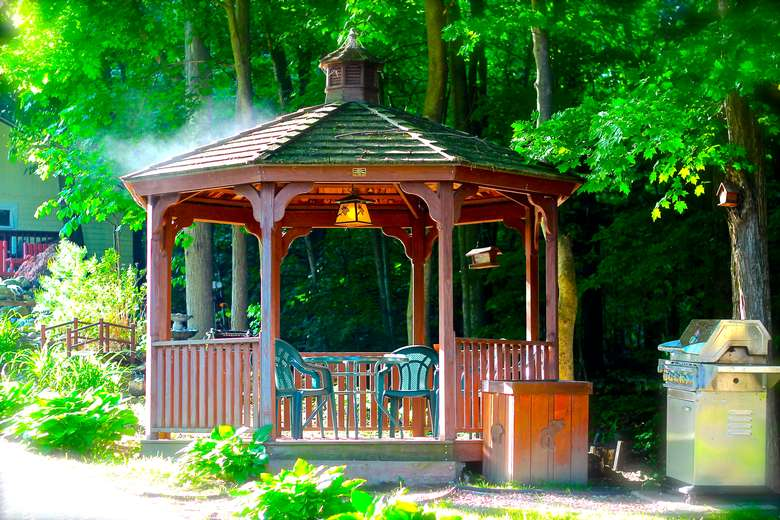 a gazebo with green chairs inside