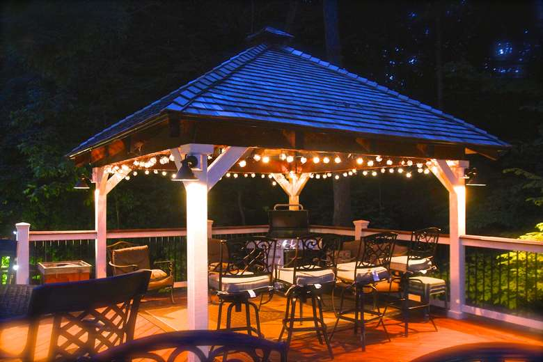 small covered area outdoors with chairs and hanging lights