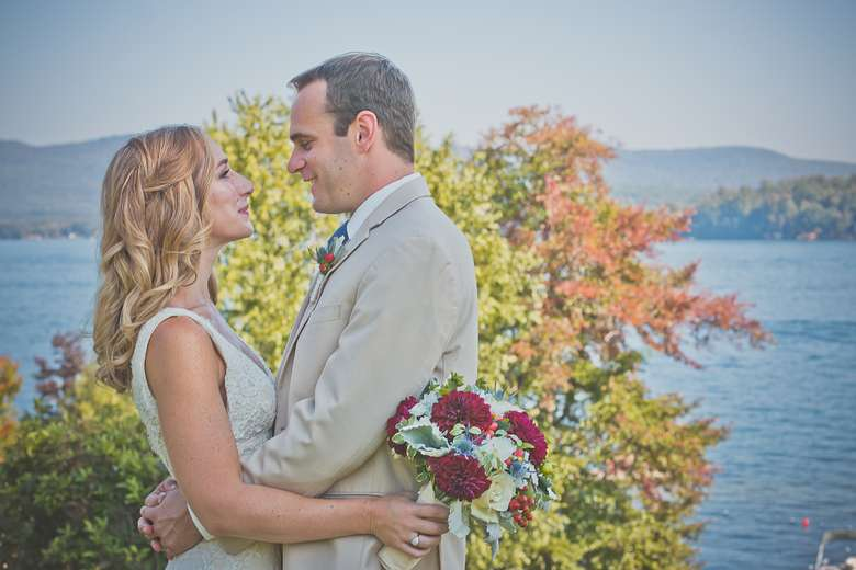 bride and groom embracing in front of lake george