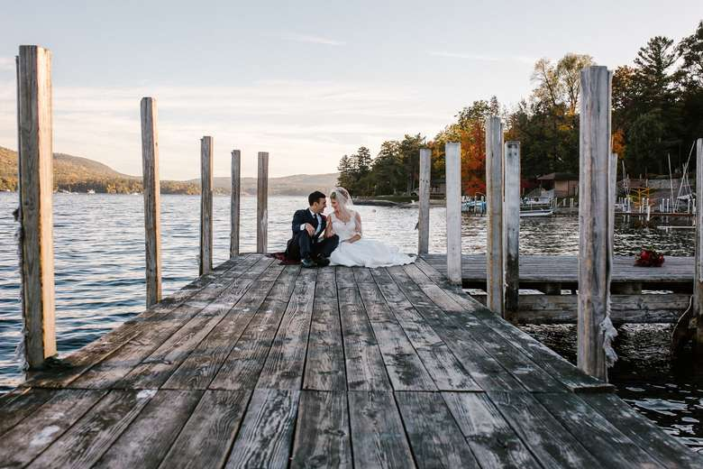 bride and groom sitting at the end of a dock on lake george