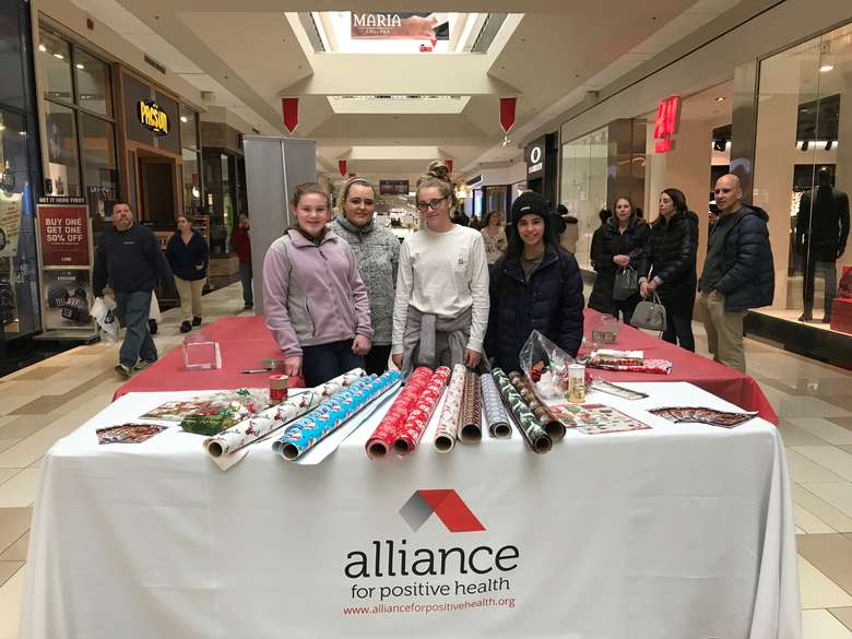four girls wrapping presents in a mall