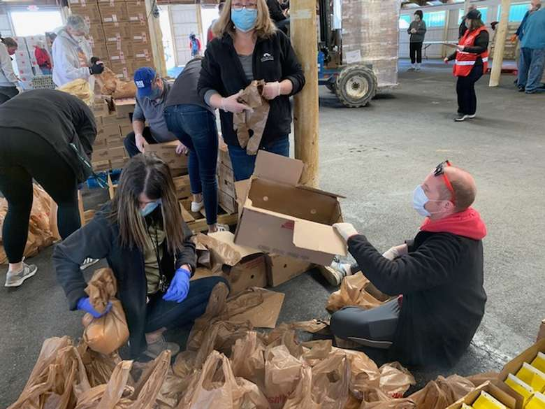 Alliance staff bagging items at food drive