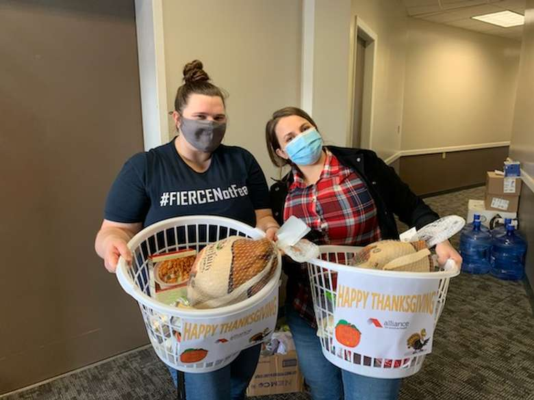Alliance staff holding baskets of Thanksgiving meal items for clients