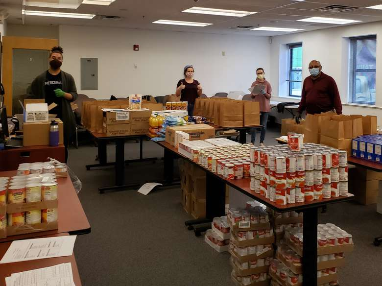 Alliance staff with food pantry items spread across tables