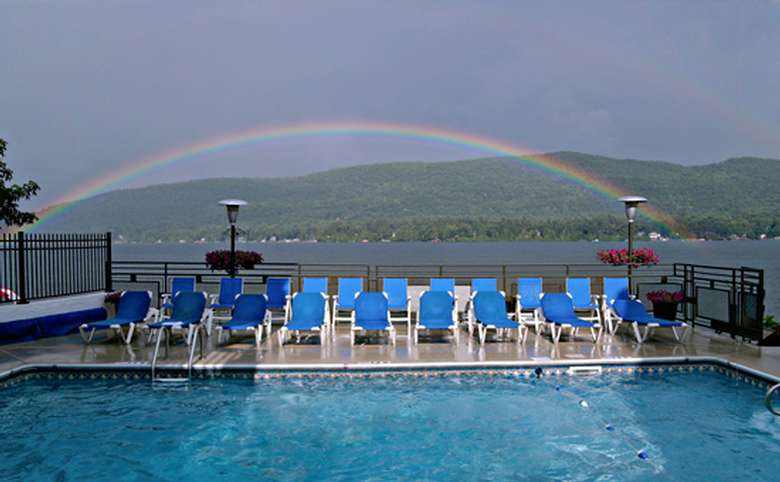 blue lounge chairs surrounding a pool overlooking lake george with a rainbow in the background