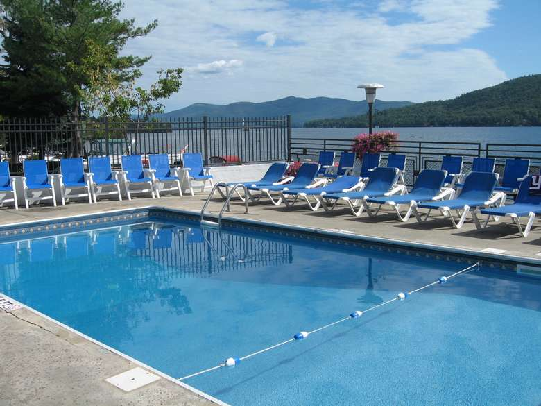 blue lounge chairs surrounding a pool overlooking lake george