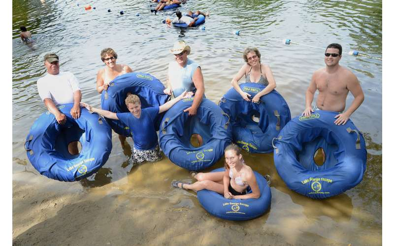 group of people holding blue tubes by the water