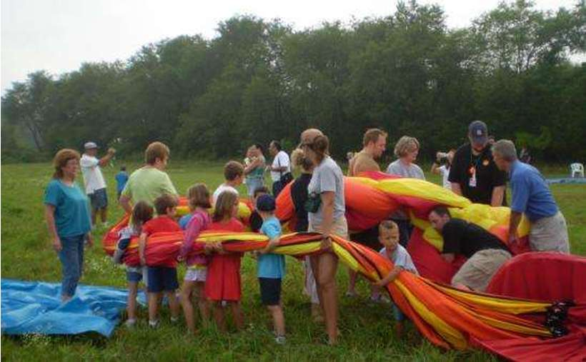 A group of adults and children working together to pack up a deflated hot air balloon