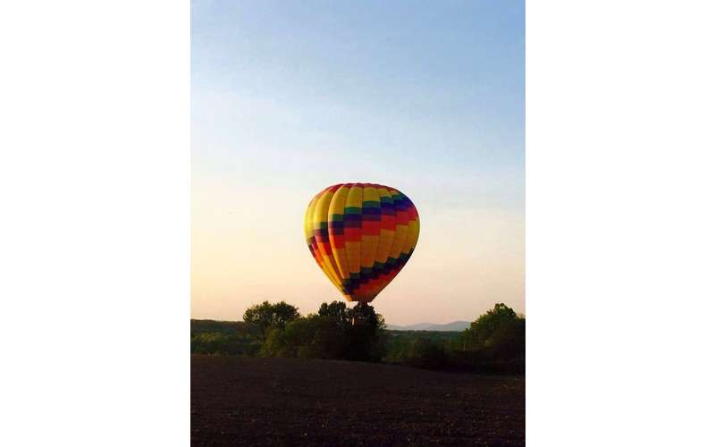 A rainbow colored hot air balloon ascending at dawn