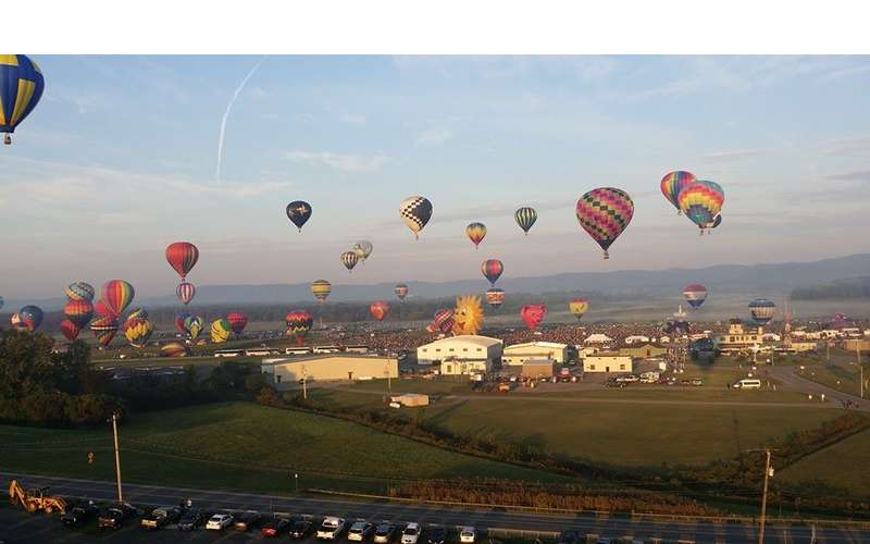 View of dozens of hot air balloons taking off at the same time at the Adirondack Balloon FEstival