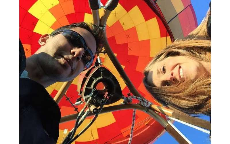 A man and a woman with a hot air balloon in the background