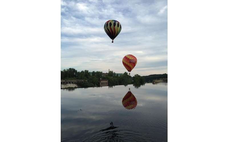 Two hot air balloons reflected in the water