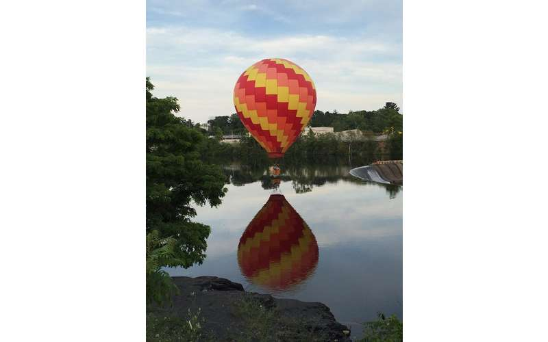 A red, orange, and yellow hot air balloon reflected in the water