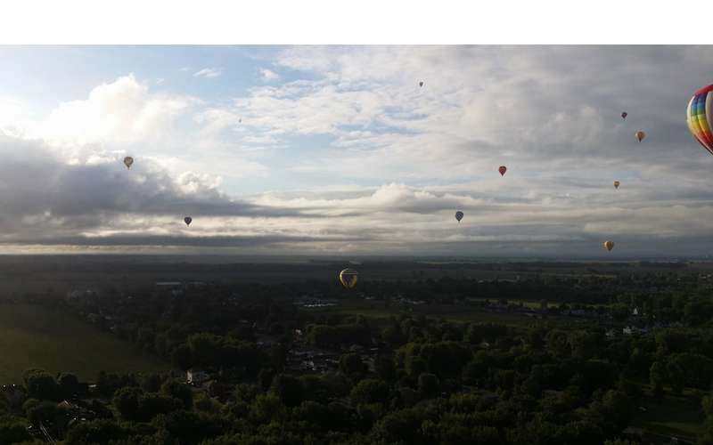 A dozen hot air balloons floating over the countryside