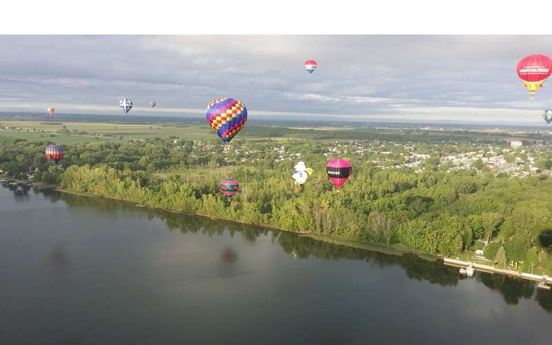 A dozen hot air balloons floating over a river