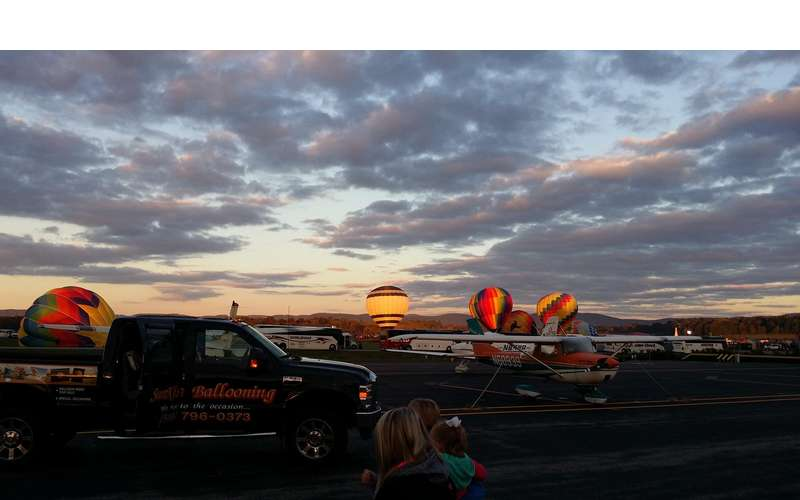 Several hot air balloons inflating at dawn at an airport