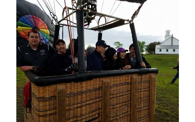 A large group in a hot air balloon basket getting ready for launch