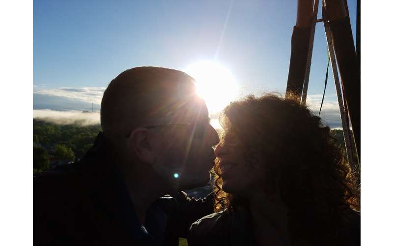 A couple about to kiss in a hot air balloon basket