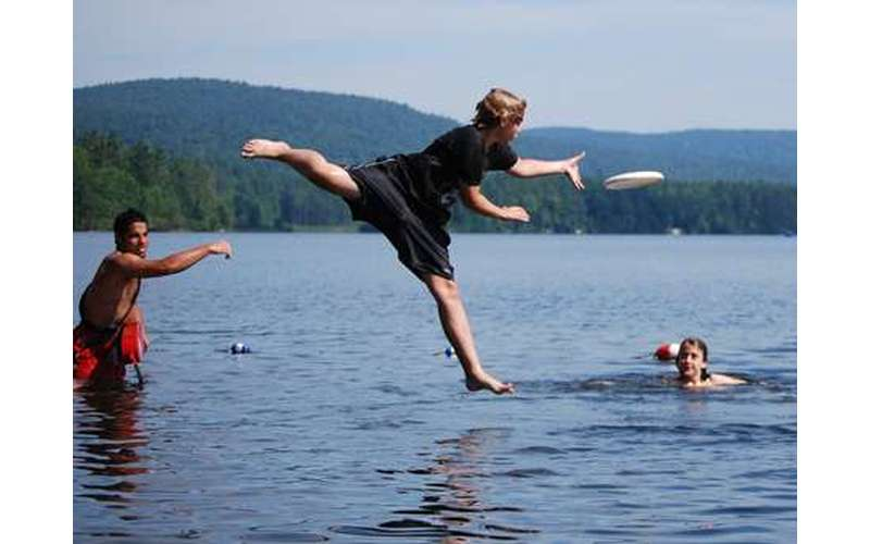 Boy jumping into the lake to catch a frisbee