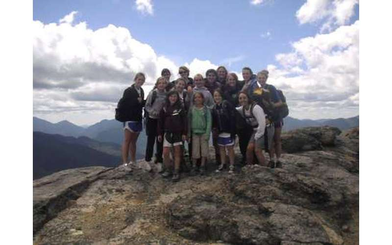 A group of kids at the top of a mountain