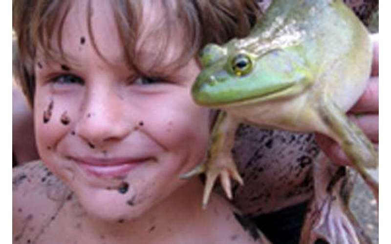 A boy with mud on his face holding a frog