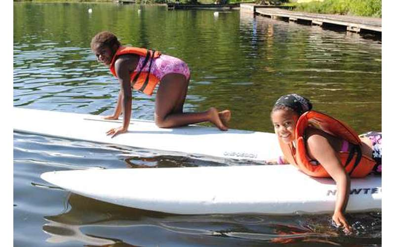 Two girls laying and kneeling on stand-up paddle boards