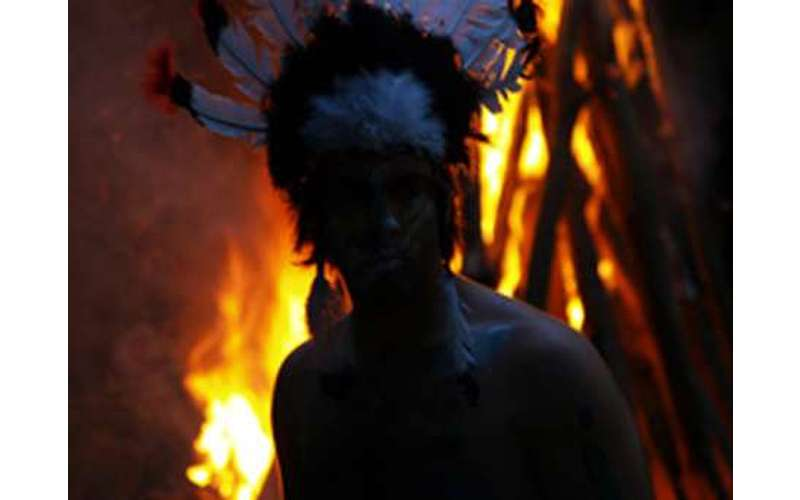 A person in a headdress in front of a fire